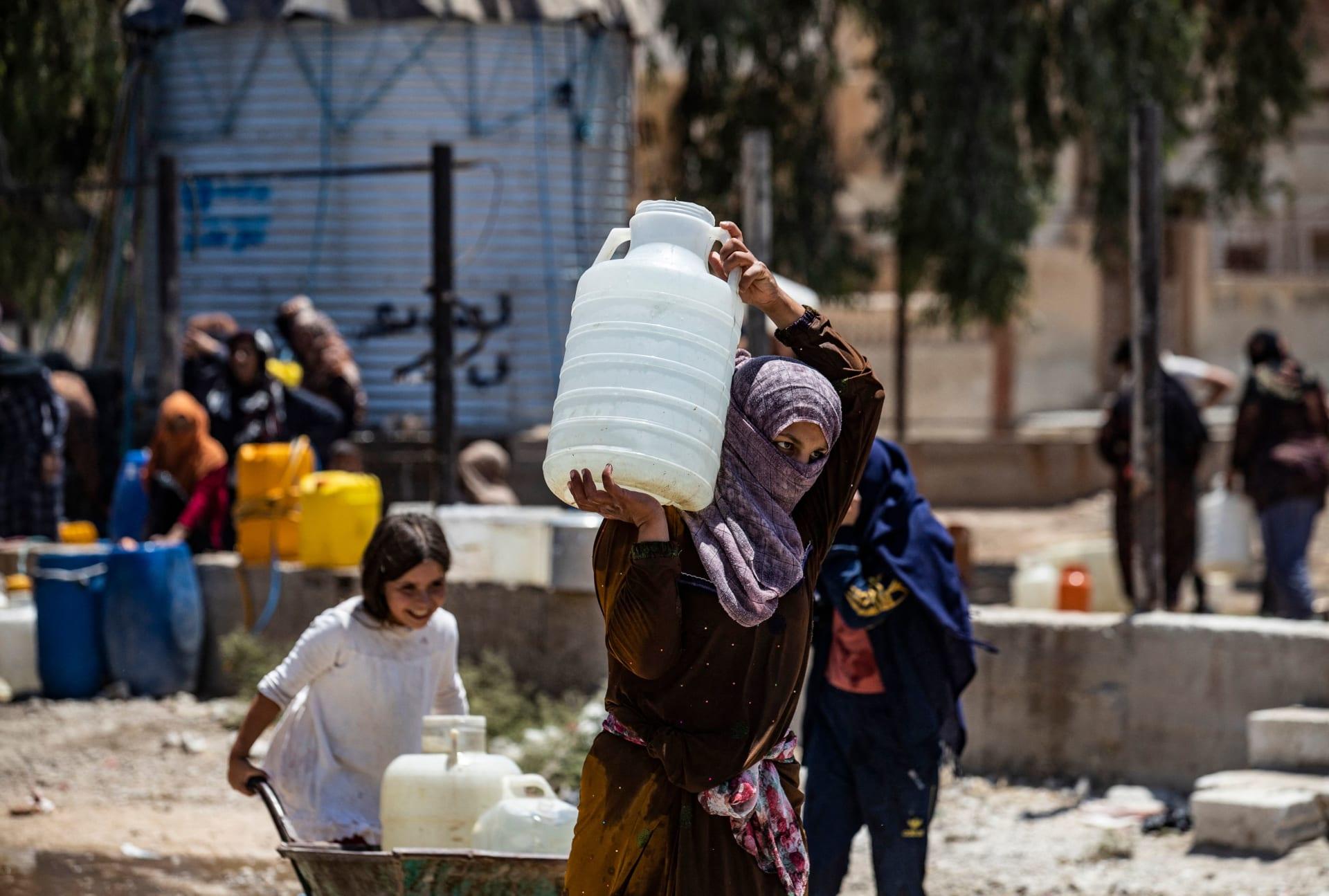 سيدة سورية تحمل حاوية مياه قدمتها منظمة اليونيسف في مدينة الحسكة شمال شرق سوريا، في 8 تموز 2021 ،