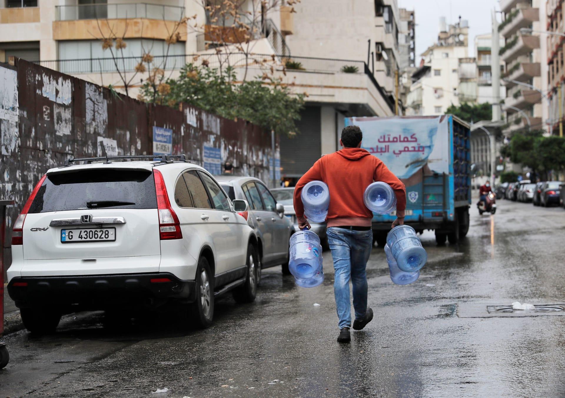 شاب يسير مع جالون ماء فارغ في شارع شبه مهجور في العاصمة بيروت، حيث يدخل لبنان يومه الأول من الإغلاق الصارم الذي فرضته السلطات في محاولة لوقف انتشار فيروس كورونا، في 14 كانون الثاني (يناير) 2021