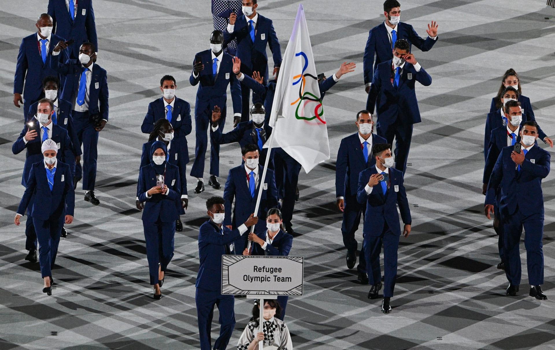 السورية يسرى مارديني تحمل علم الفريق الأولمبي للاجئين مع الإريتري الأصل تاتلويني غابرييسوس