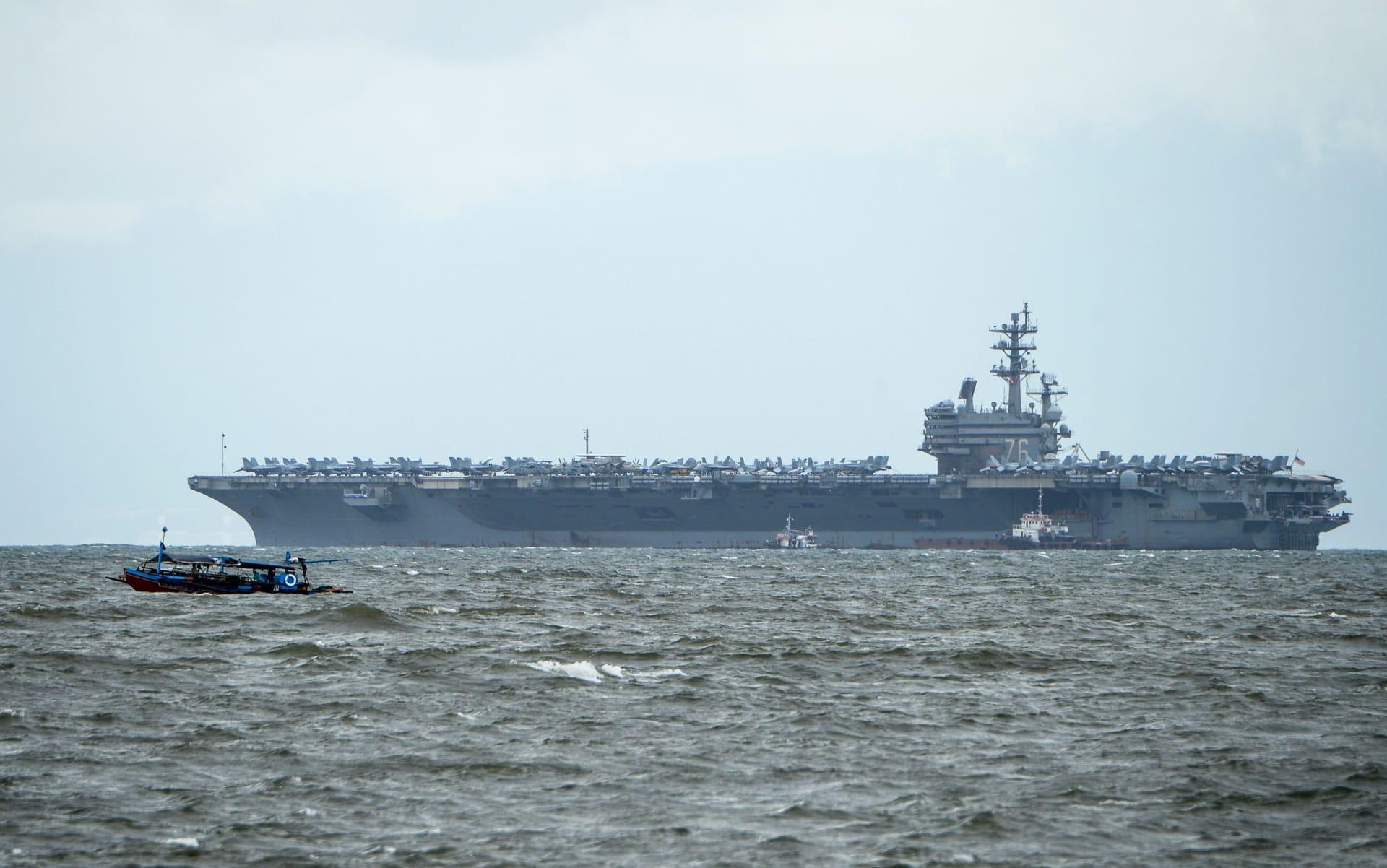 قارب صيد فلبيني (يسار) يمر بسرعة متجاوزًا يو إس إس رونالد ريغان راسيًا في خليج مانيلا في 7 أغسطس، 2019.