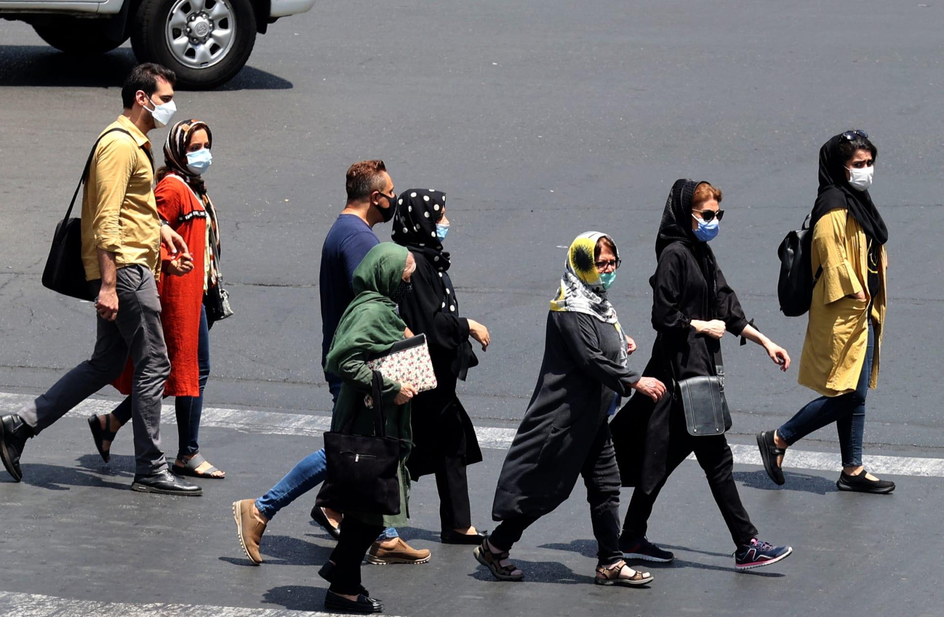 إيرانيون يرتدون أقنعة بسبب جائحة كورونا يعبرون شارعًا في العاصمة طهران، في 3 يوليو 2021.