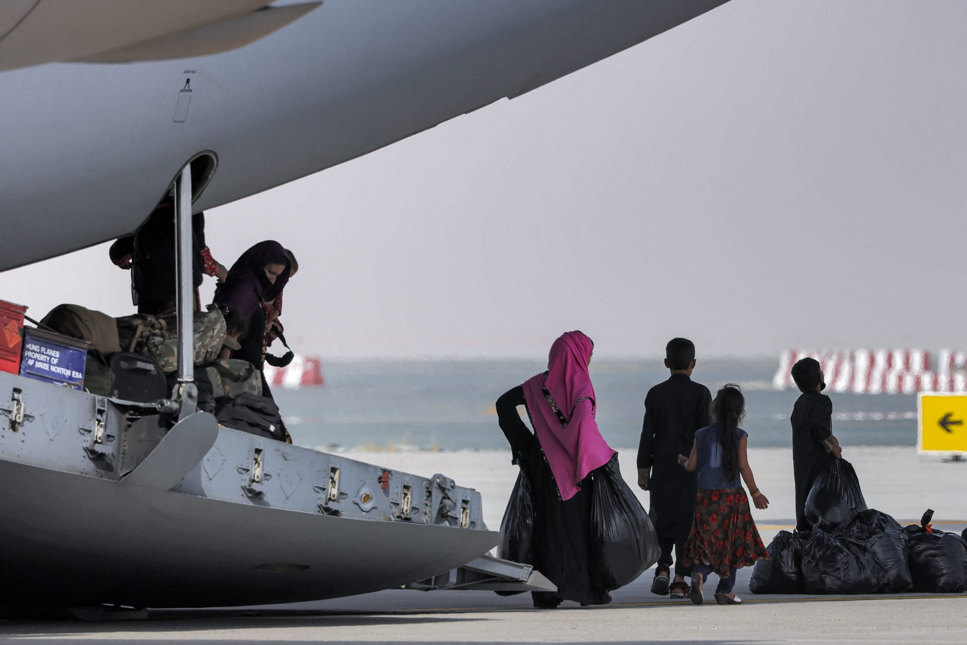 أشخاص ينزلون من طائرة نقل عسكرية تابعة للقوات الجوية الملكية تحمل أشخاص تم إجلاؤهم من أفغانستان وتصل إلى مطار آل مكتوم الدولي في الإمارات العربية المتحدة في 19 أغسطس 2021.