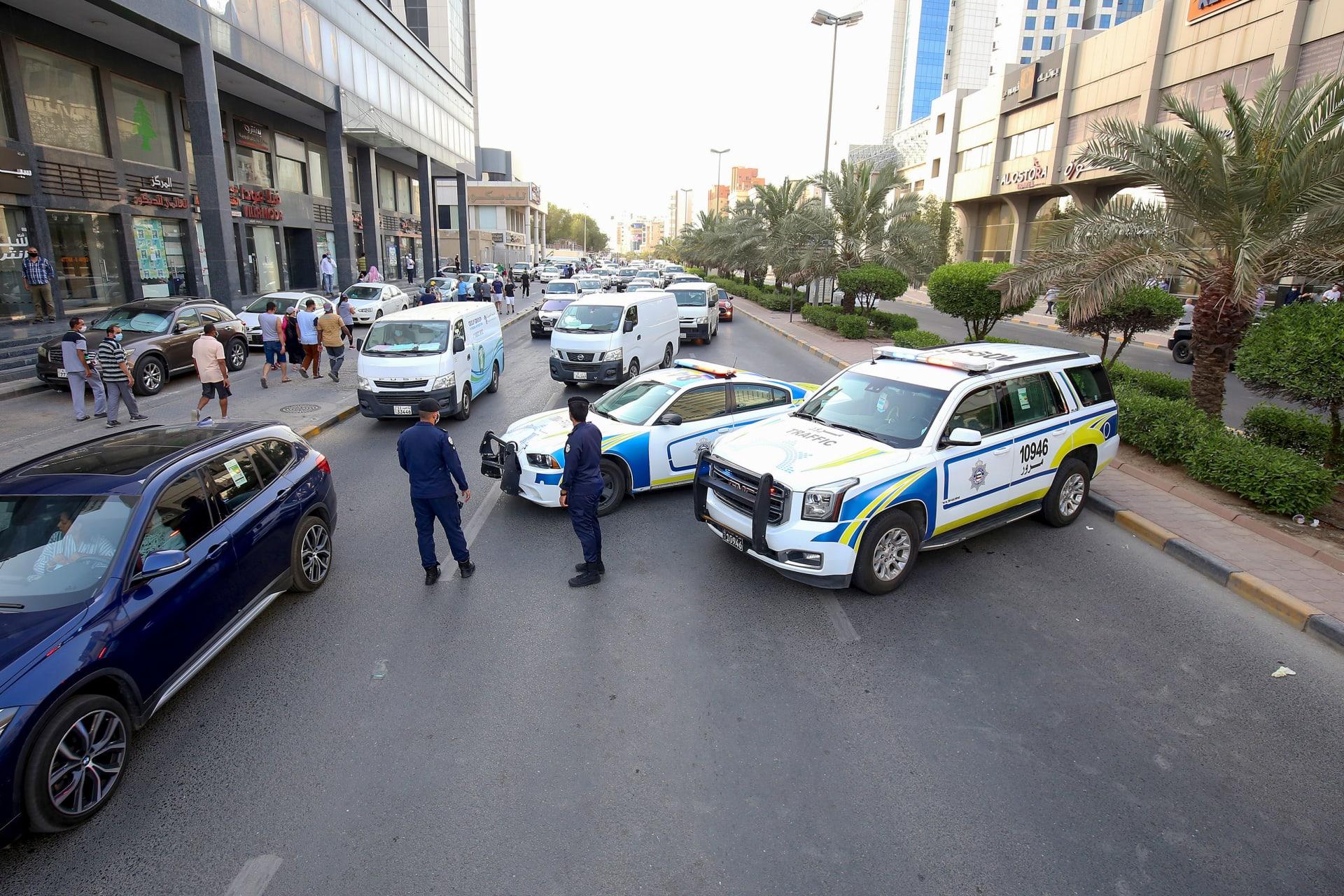 ناصر من الشرطة الكويتية يقفون نقطة تفتيش عند المدخل المؤدي إلى حي حولي بمدينة الكويت في 29 مايو 2020