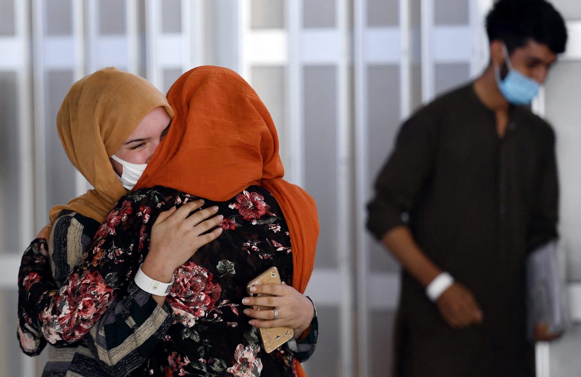 امرأة تعانق شقيقة زوجها (يسار) عند وصولها مع لاجئين أفغان آخرين على متن رحلة في مطار دالاس الدولي في شانتيلي، فيرجينيا في 23 أغسطس 2021.