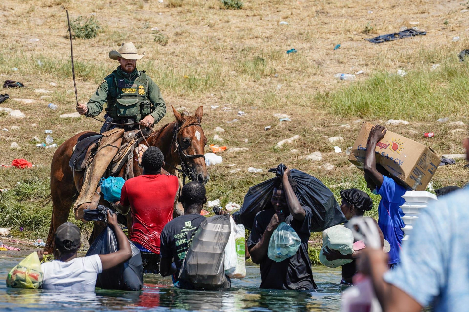 دوريات الحدود بالولايات المتحدة على ظهور الخيل في مواجهة المهاجرين الهايتيين على ضفاف نهر ريو غراندي بولاية تكساس - 19 سبتمبر 2021.