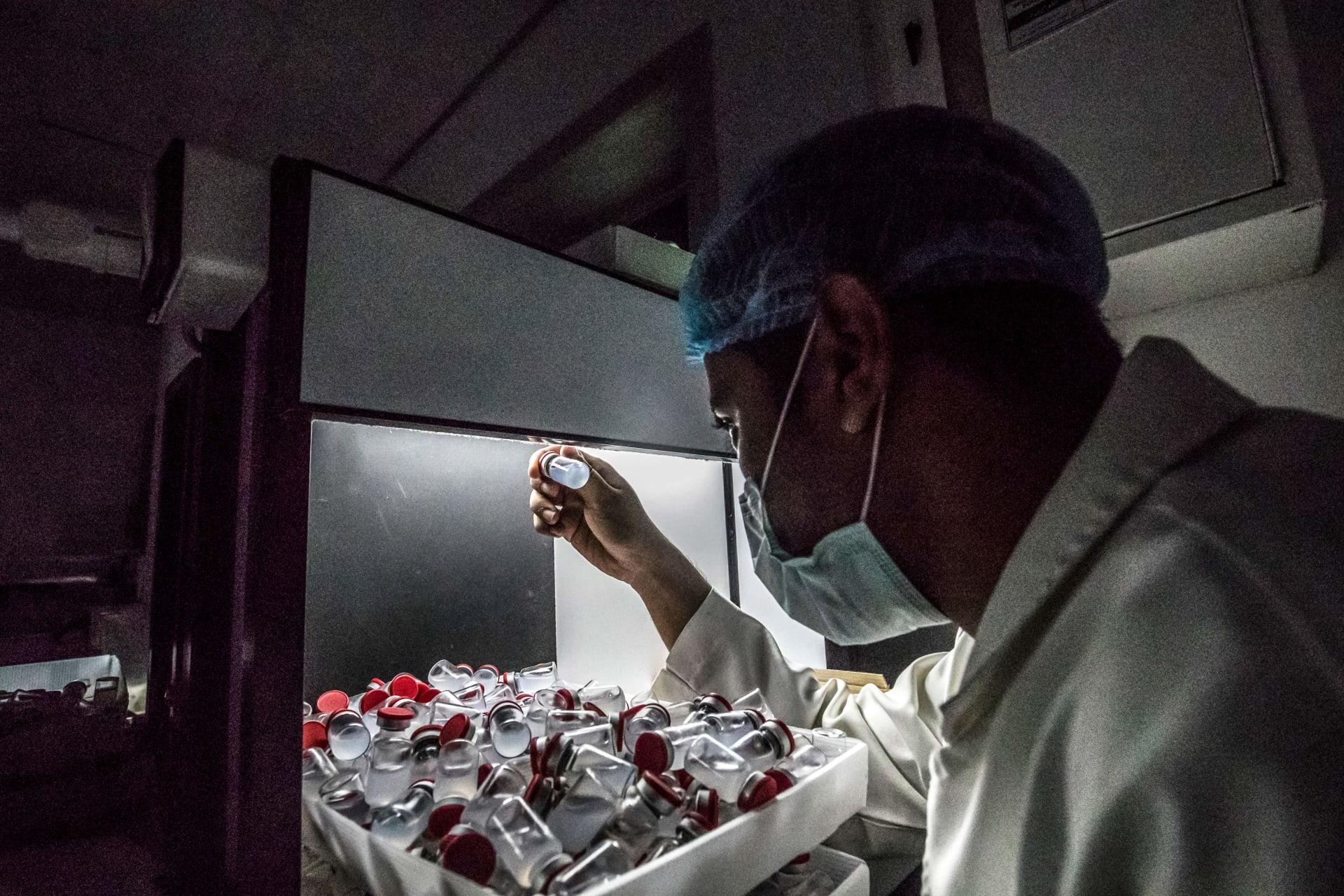 صورة أرشيفية - فني معمل يحمل قنينة لقاح سينوفاك الصيني، الذي تنتجه شركة VACSERA المصرية، في 1 سبتمبر 2021.