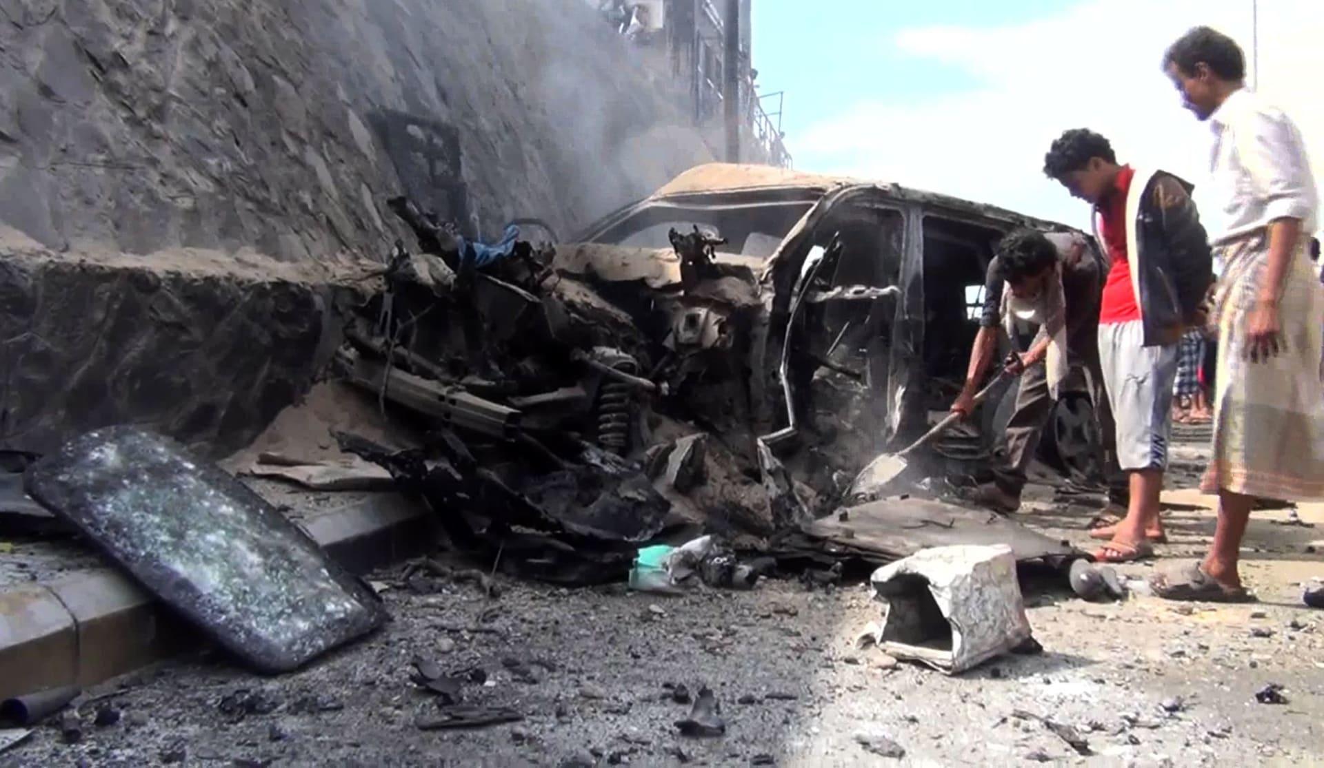 أرشيفية - يمنيون يتفقدون السيارة المحطمة لمحافظ عدن، جعفر سعد، بعد انفجار استهدف موكبه في عدن، مما أسفر عن مقتله هو وبعض حراسه الشخصيين في 6 ديسمبر / كانون الأول 2015