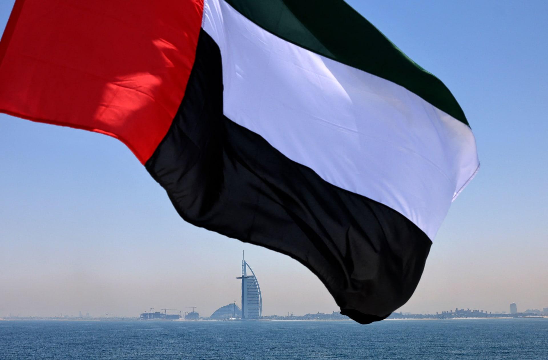 علمًا إماراتيًا يرفرف فوق مرسى دبي مع فندق برج العرب في الخلفية