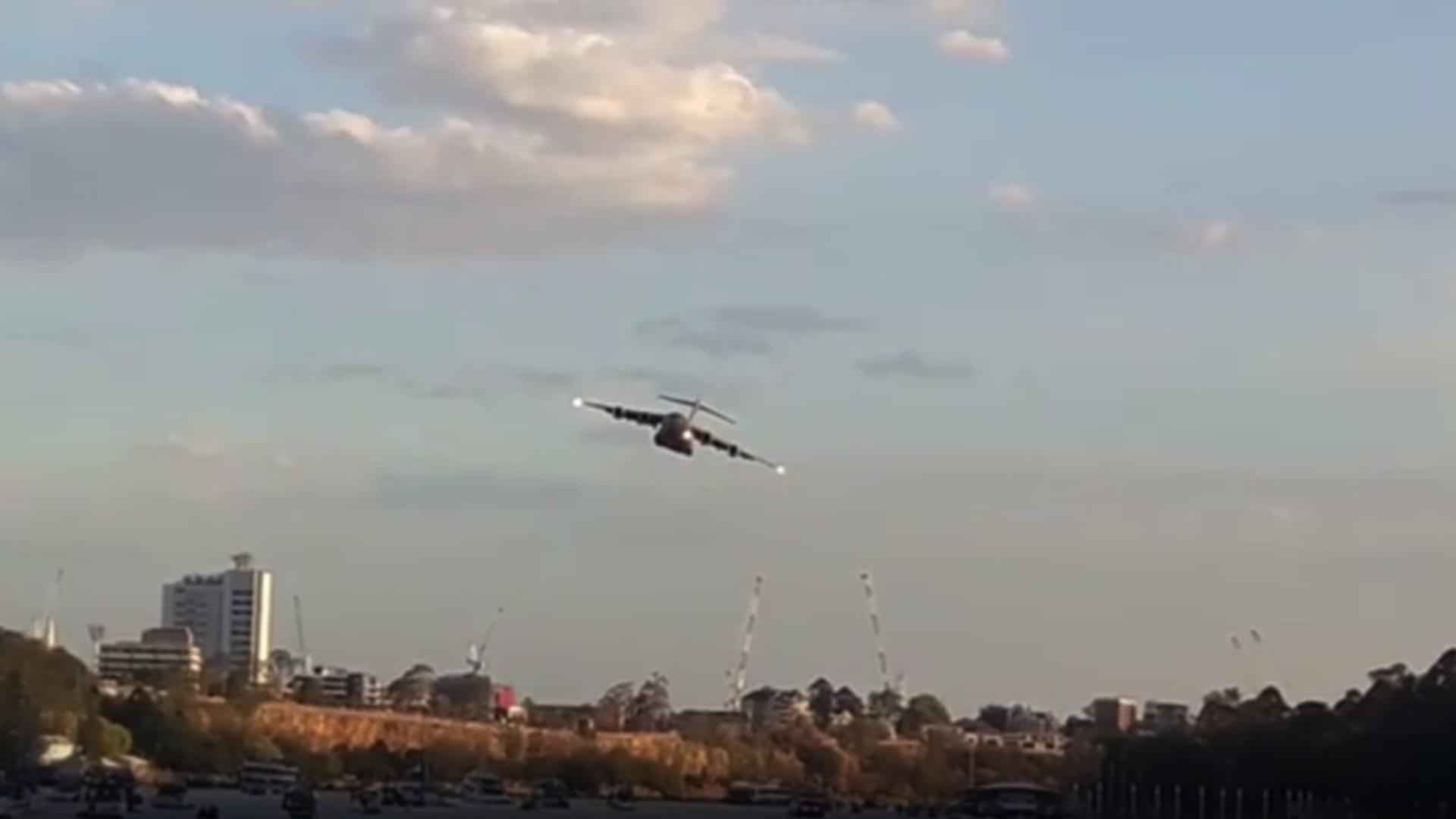 شاهد.. طائرة عسكرية ضخمة تحلق بين المباني على ارتفاع منخفض في أستراليا