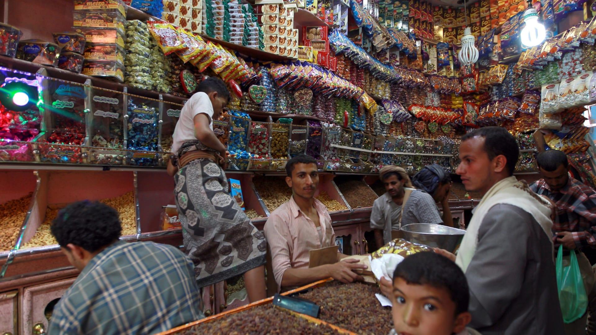 بائع في العاصمة اليمنية صنعاء يبيع الحلويات لبعض زبائنه بمناسبة العيد