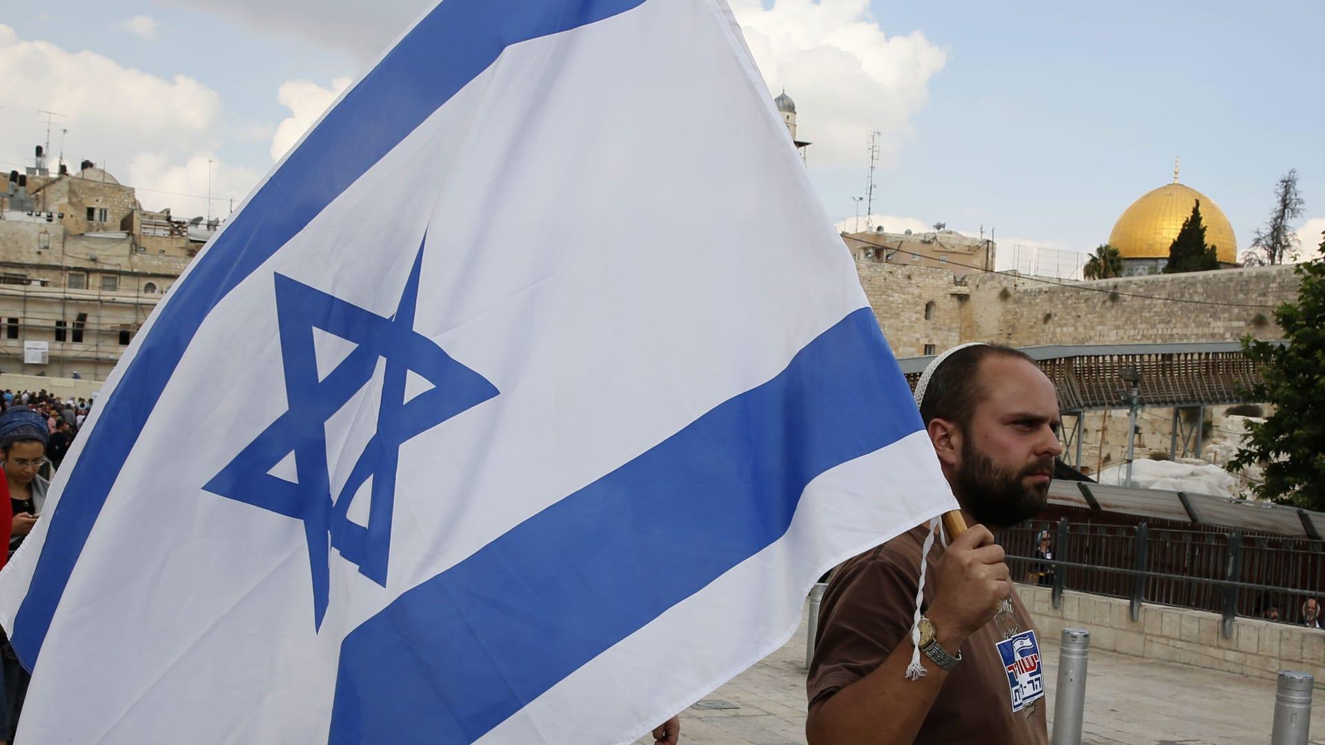 أحد أفراد اليمين الإسرائيلي المتطرف يحمل العلم الإسرائيلي قرب المسجد الأقصى بالقدس.
