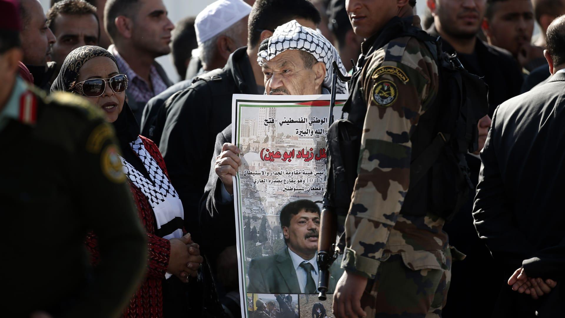 فلسطيني يرفع ملصقا يحمل صورة زياد أبو عين خلال مشاركته في جنازته.