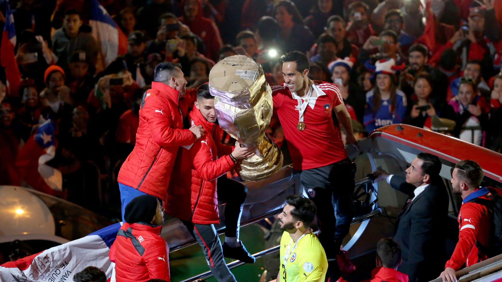 """لاعبو المنتخب التشيلي يحملون الكأس على متن حافلتهم بعد فوزهم بلقب بطولة """"كوبا أمريكا."""""""
