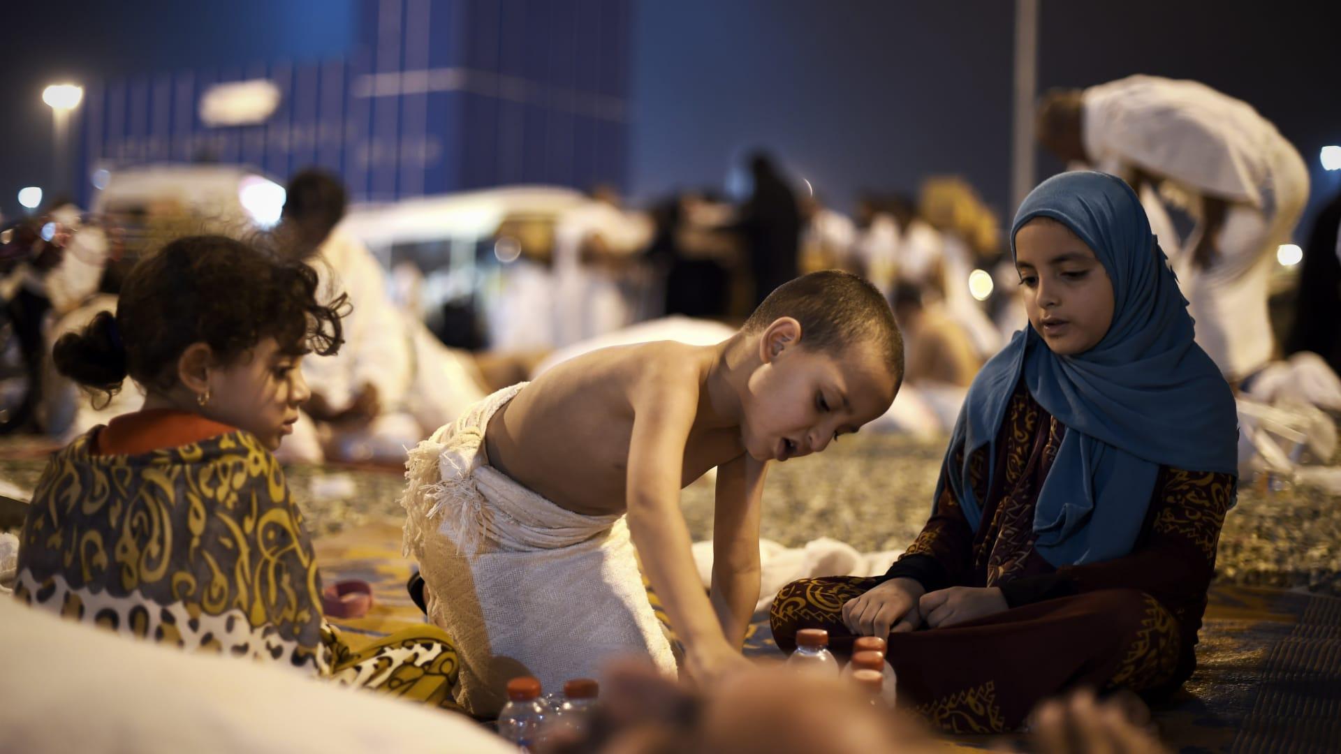 أطفال يجلسون بعد وصولهم مع ذويهم إلى مزدلفة قادمين من عرفة في مكة