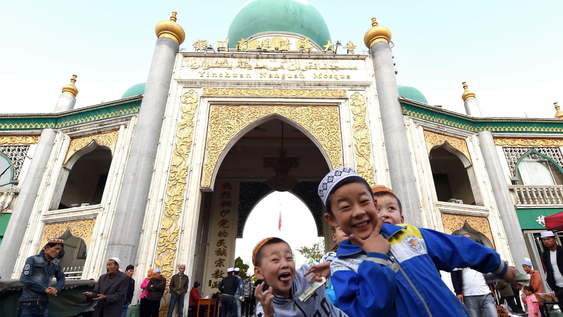 أطفال يبتسمون للكاميرا بعد أدائهم صلاة العيد في الصين