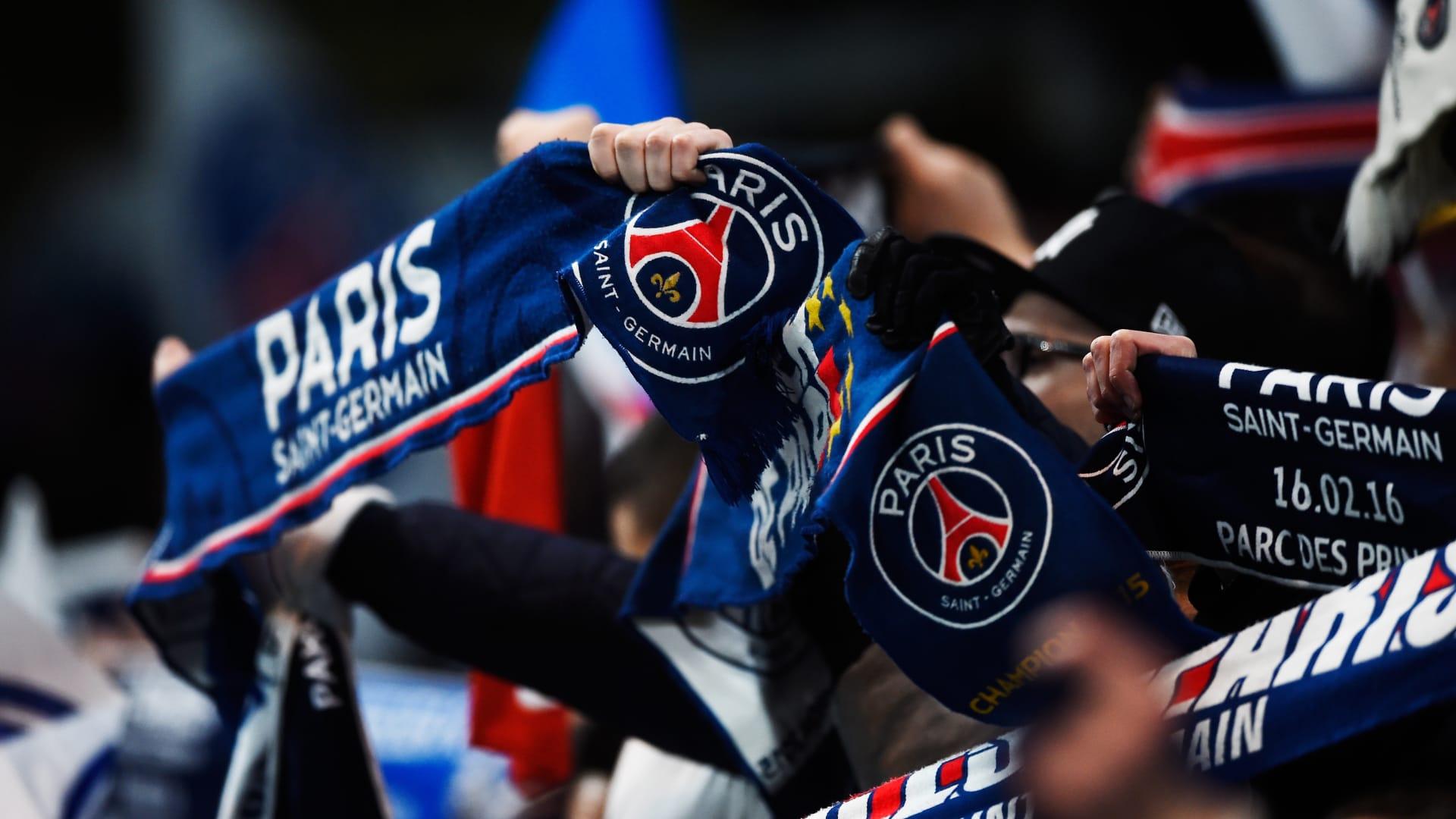 مشجعون لنادي باريس سان جيرمان يحملون أوشحة تحمل اسم فريقهم في المباراة أمام فريقهم.