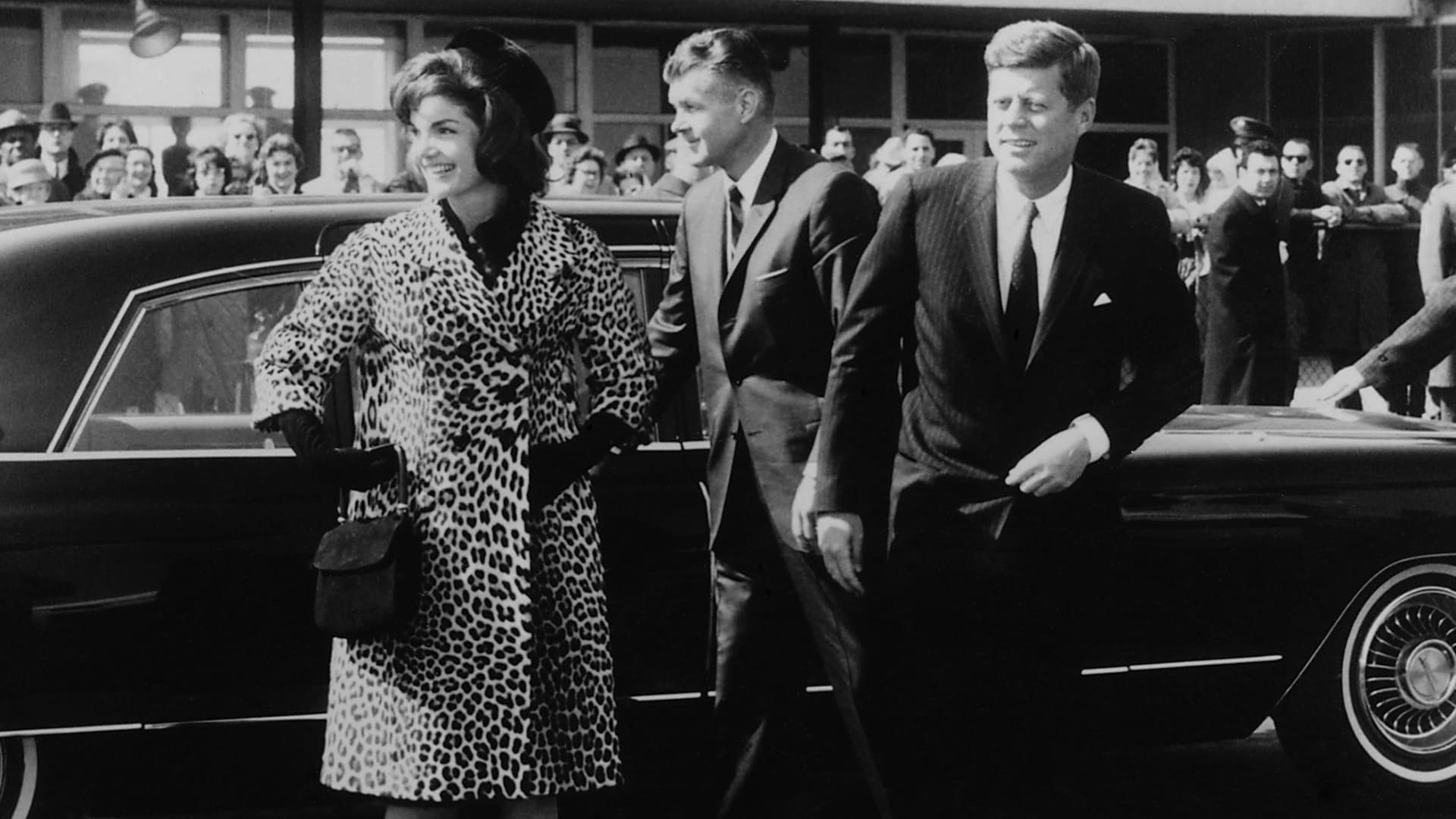 جاكي كينيدي، برفقة الرئيس كينيدي، ترتدي معطفاً من تصميم أوليغ كاسيني من جلد الفهد في العام 1962.