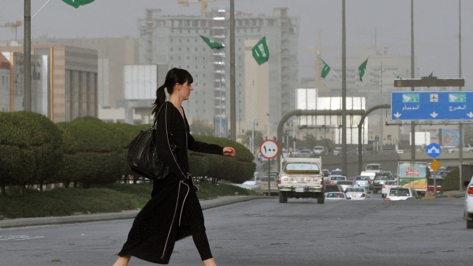صورة ارشيفية لامرأة وافدة تقطع أحد شوارع الرياض العام 2011