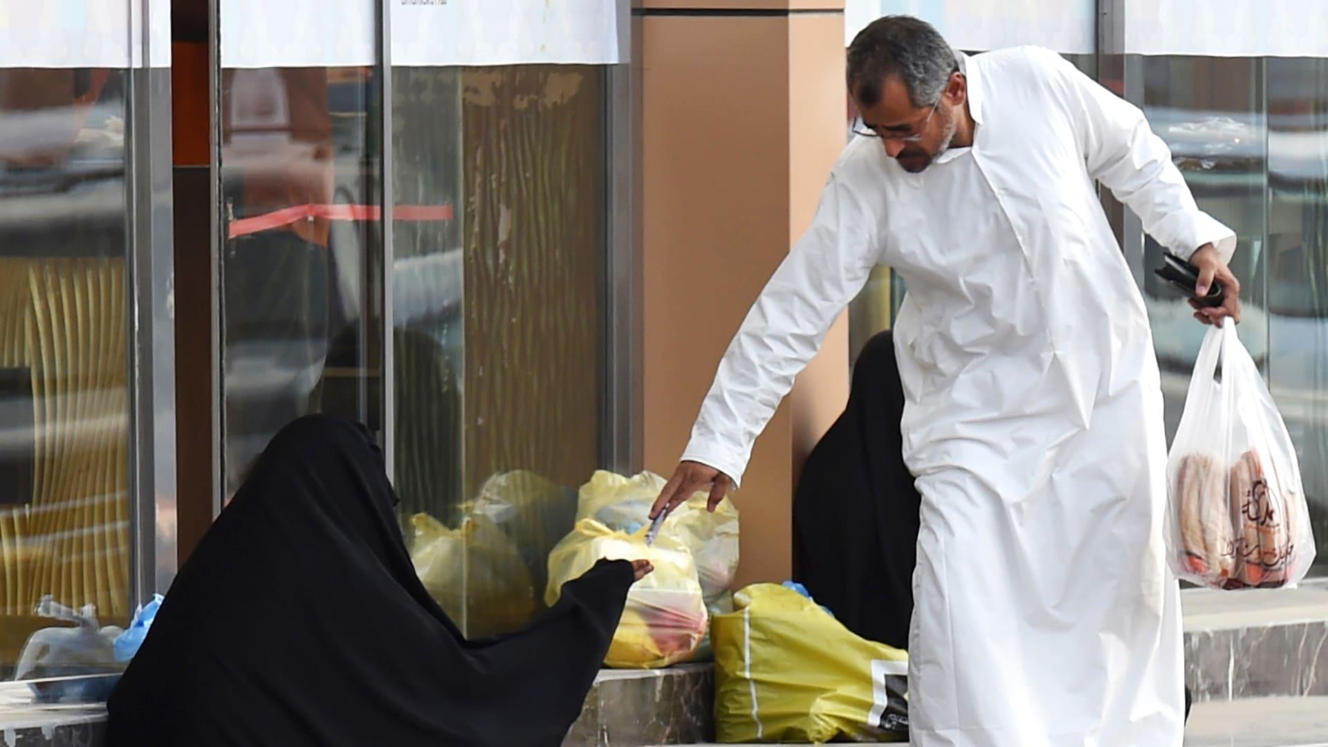 صورة ارشيفية لرجل يعطي مالا لامرأة تطلب المساعدة في السعودية
