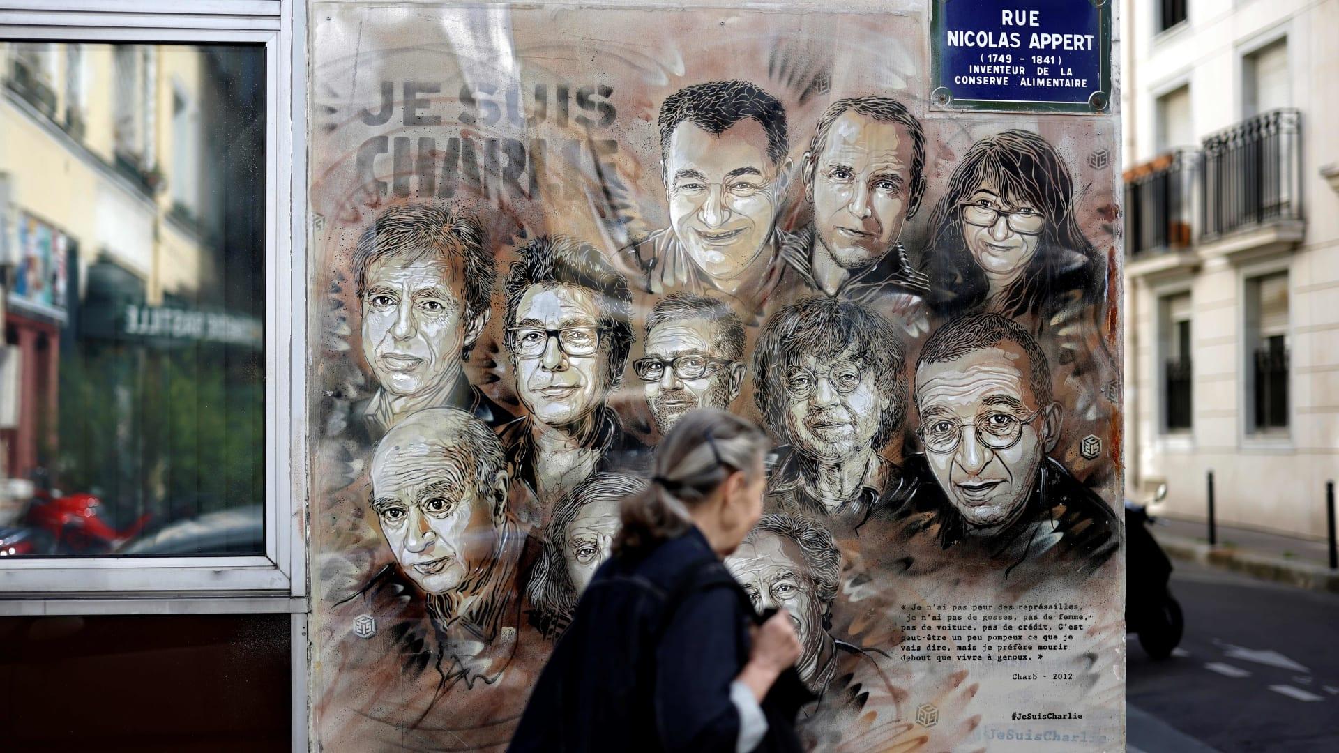 سيدة تمر بجوار لافتة تحيي ذكرى الضحايا في الهجوم على مقر صحيفة شارلي إبدو الفرنسية في 2015