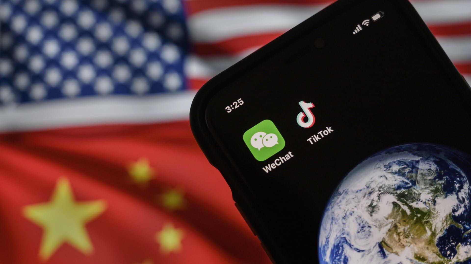 رسم يبيّن هاتفاً محمولاً يعرض تطبيقي WeChat و TikTok أمام شاشة تعرض علمي الولايات المتحدة والصين