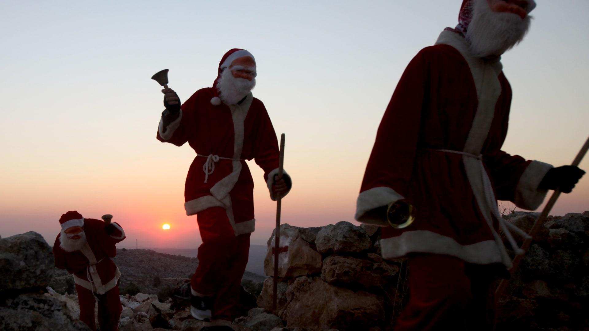 """صورة ارشيفية (تعبيرية) لأشخاص يرتدون زي """"بابا نويل"""" احتفالا بعيد الميلاد في قرى فلسطينية"""