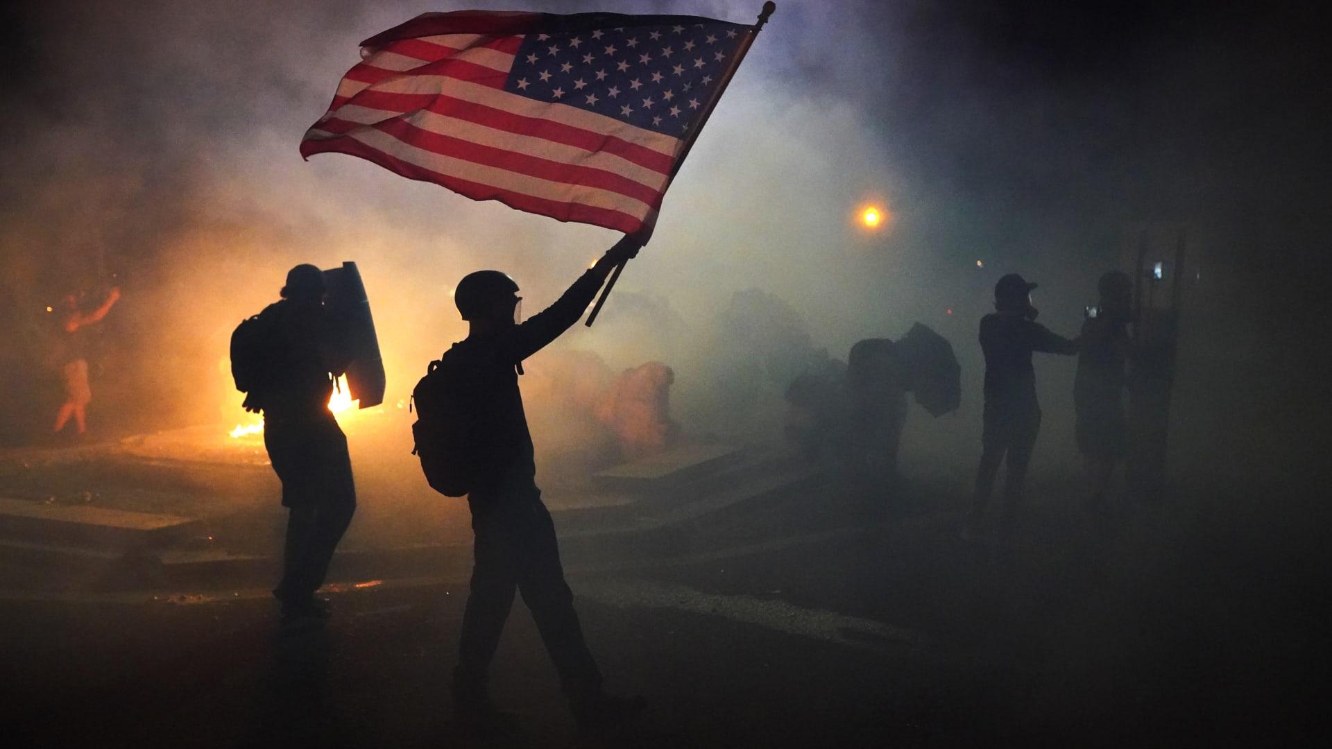 متظاهر يرفع العلم الأمريكي وسط الغاز المسيل للدموع