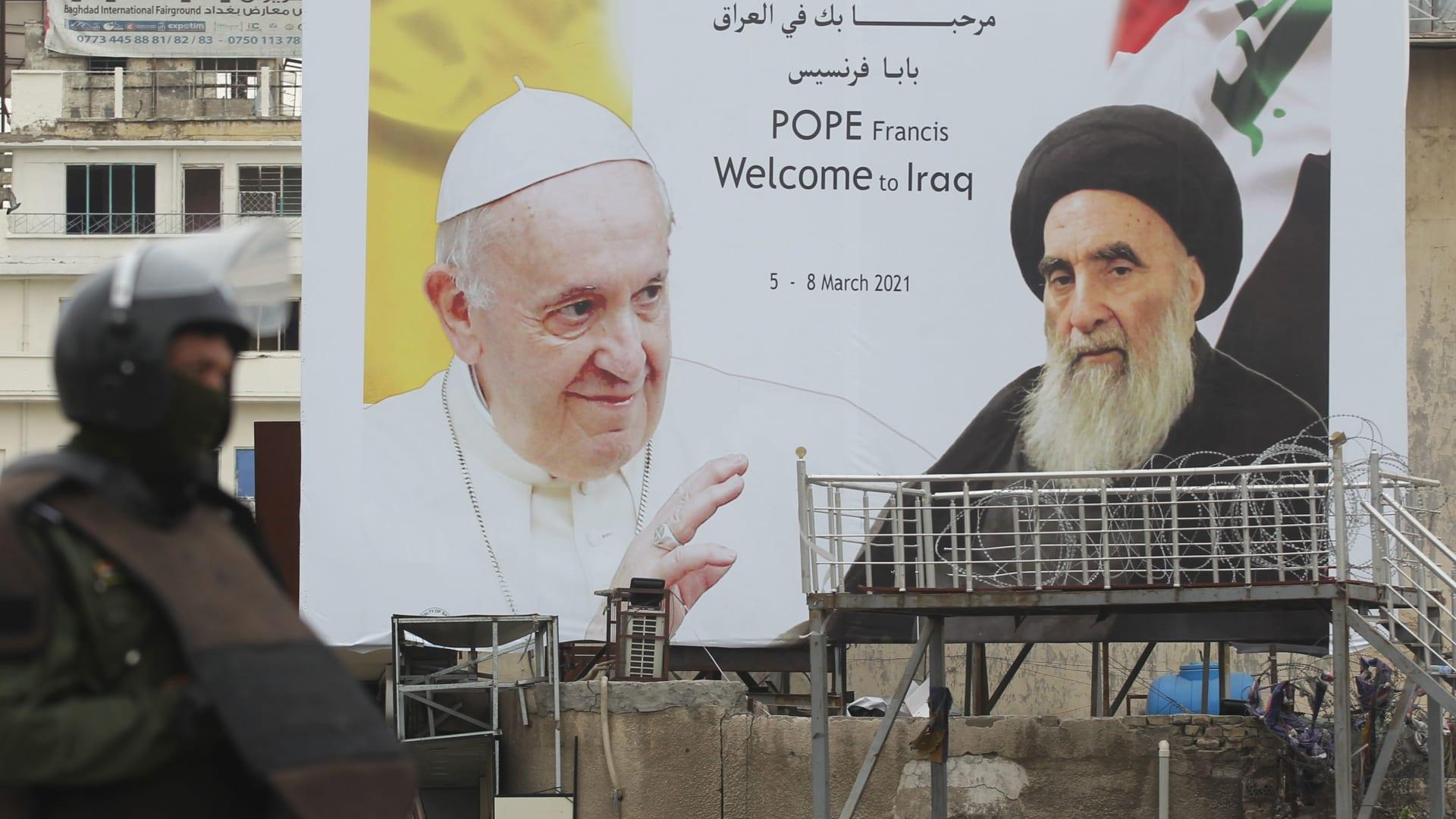 حارس أمن عراقي يقف أمام لوحة إعلانية ضخمة تحمل صور البابا فرنسيس والسيستاني وسط بغداد
