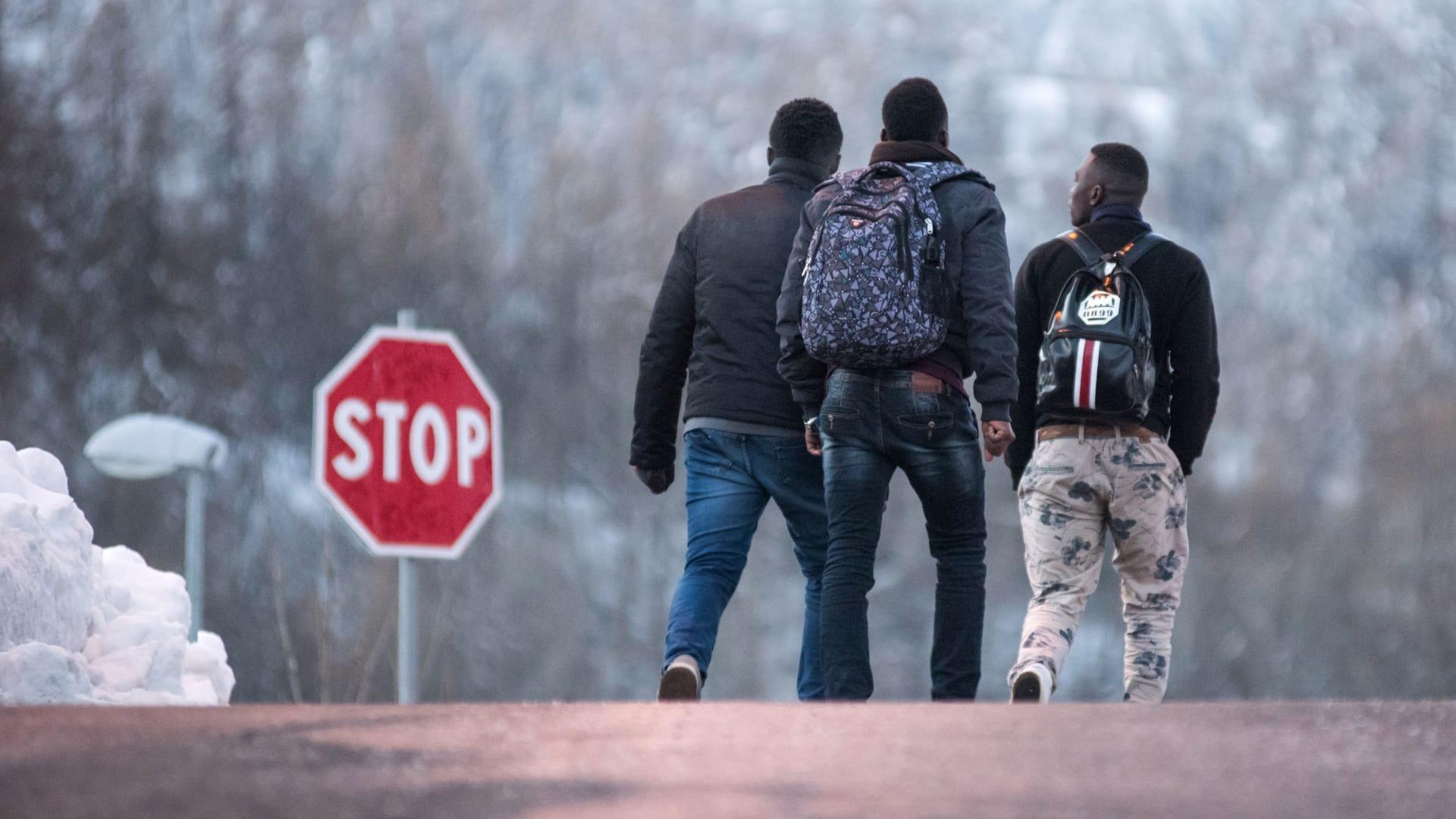 مهاجرون يسيرون في اتجاه  ممر مغطى بالثلوج لعبور الحدود بين إيطاليا وفرنسا