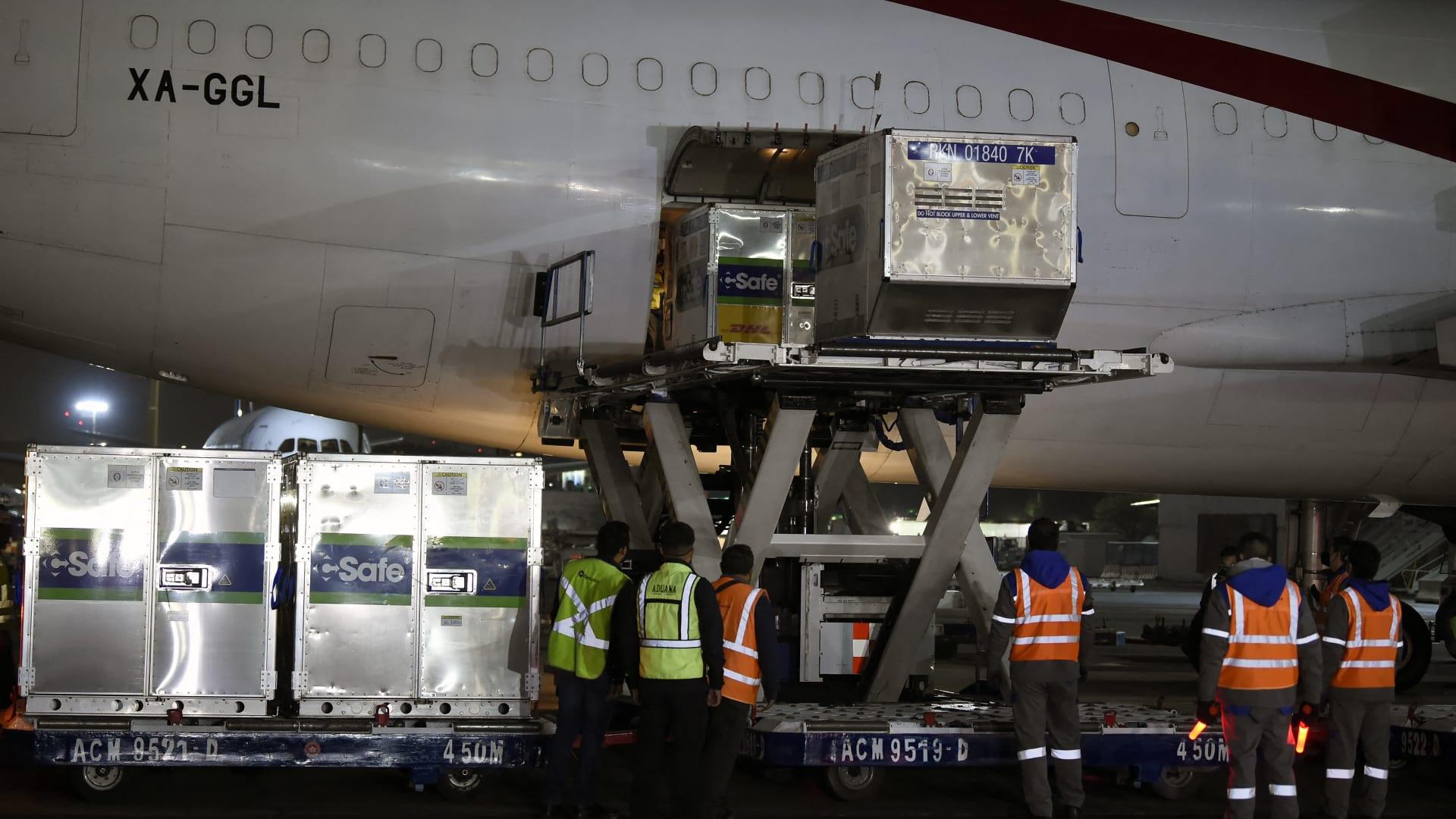 يقوم موظفون بتفريغ حاويات الشحن من لقاح AstraZeneca قادمة من الولايات المتحدة في مطار بينيتو خواريز الدولي في مكسيكو سيتي في 28 مارس 2021