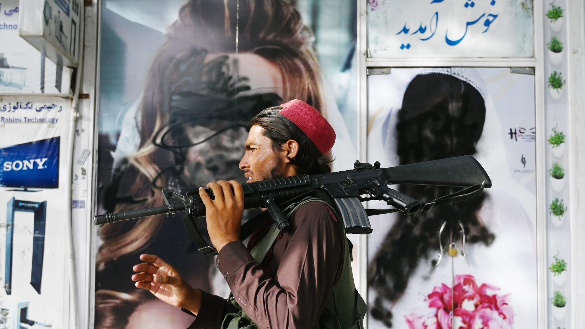 قاتل من طالبان يمشي أمام صالون تجميل مع صور لنساء مشوهات بالطلاء بالرش في شار ناو في كابول في 18 أغسطس 2021