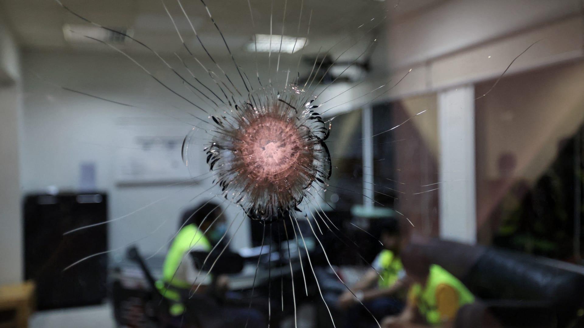 صورة لموظفين سعوديين خلف شظايا زجاج مثقوب بمطار أبها في 31 أغسطس بعد هجوم بطائرة مسيرة على المطار