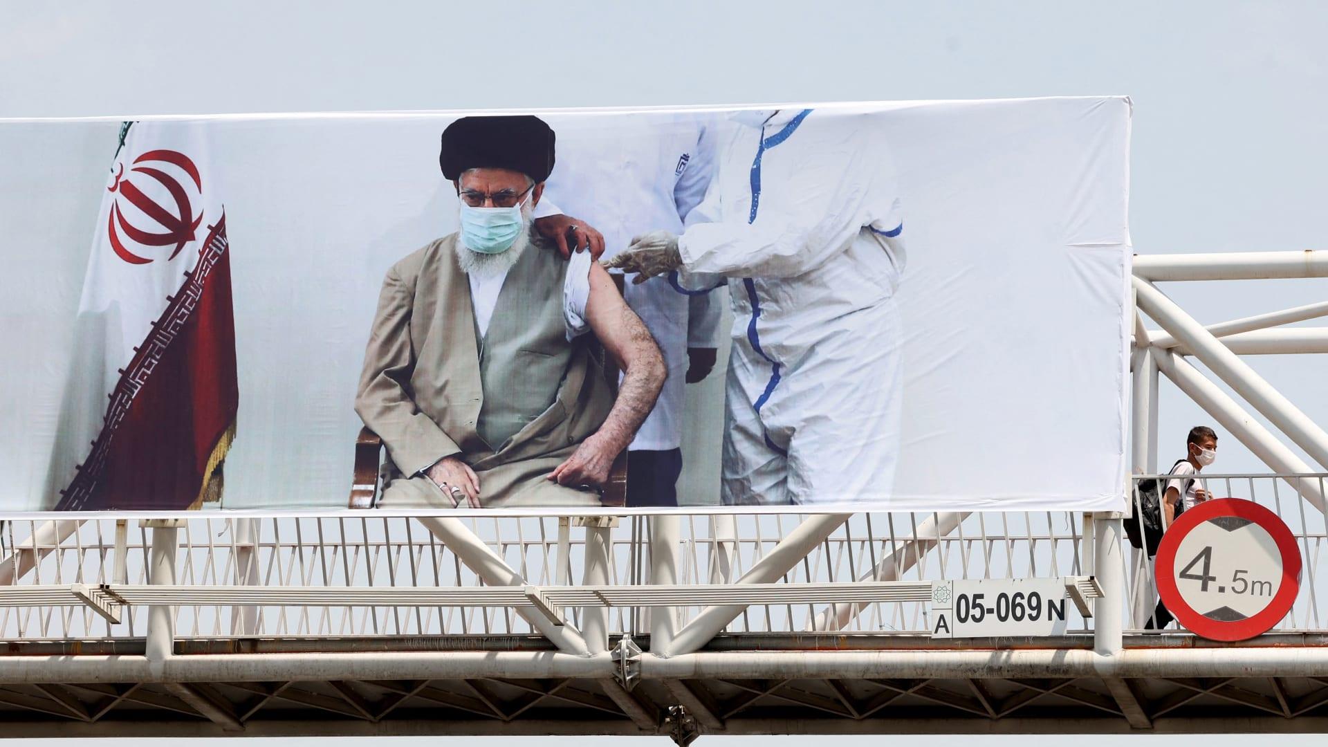 لافتة تظهر المرشد الإيراني علي خامنئي وهو يتلقى لقاحًا ضد فيروس كورونا، في العاصمة طهران - في 3 يوليو / تموز 2021.