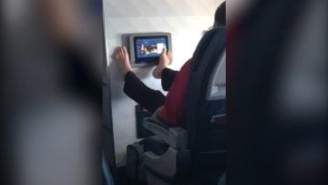 مسافر يستخدم شاشة الطائرة بقدميه