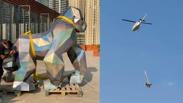 """تمثالا غوريلا ونمر """"يتأرجحان"""" من طائرة هليكوبتر فوق ناطحات سحاب دبي"""