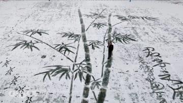 مدرس فنون في الصين يرسم لوحة عملاقة على الثلج لإبهار طلابه
