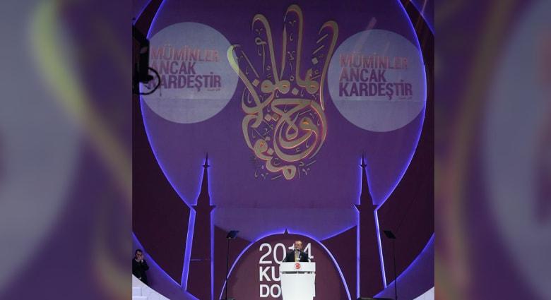 """جدل بعد ظهور آية """"إنما المؤمنون إخوة"""" مرسومة على شكل """"رابعة"""" خلف أردوغان"""