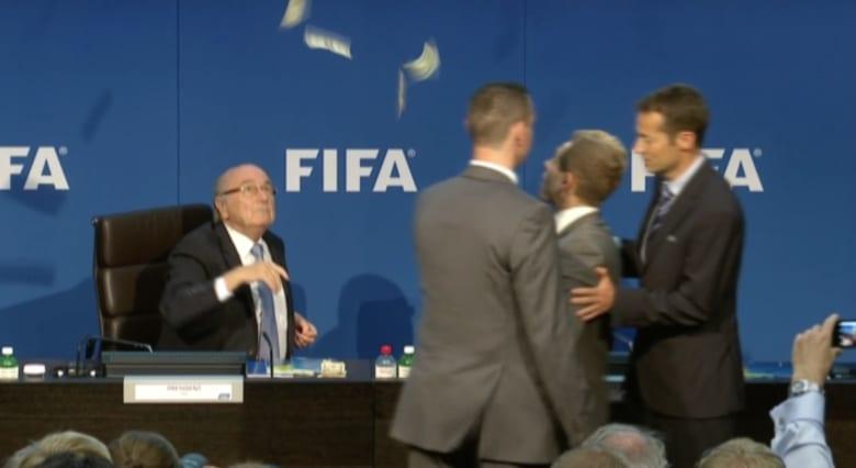 """شاهد.. """"رشقة من النقود"""" على رأس بلاتر خلال توجهه لعقد مؤتمر صحفي بمقر الفيفا"""