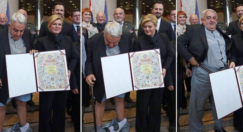 """بالفيديو.. سقوط سروال رئيس لجنة """"هيلسنكي"""" لحقوق الإنسان أمام رئيسة كرواتيا أثناء تكريمه"""