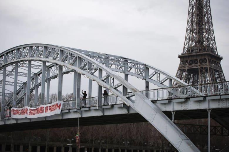"""ناشطة من """"فيمن"""" تمثل دور سيدة مشنوقة احتجاجًا على زيارة روحاني لفرنسا"""