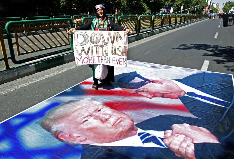 """امرأة إيرانية تدوس على صورة للرئيس الأمريكي دونالد ترامب ورئيس الوزراء الإسرائيلي بنيامين نتنياهو خلال مسيرة بمناسبة """"يوم القدس"""""""