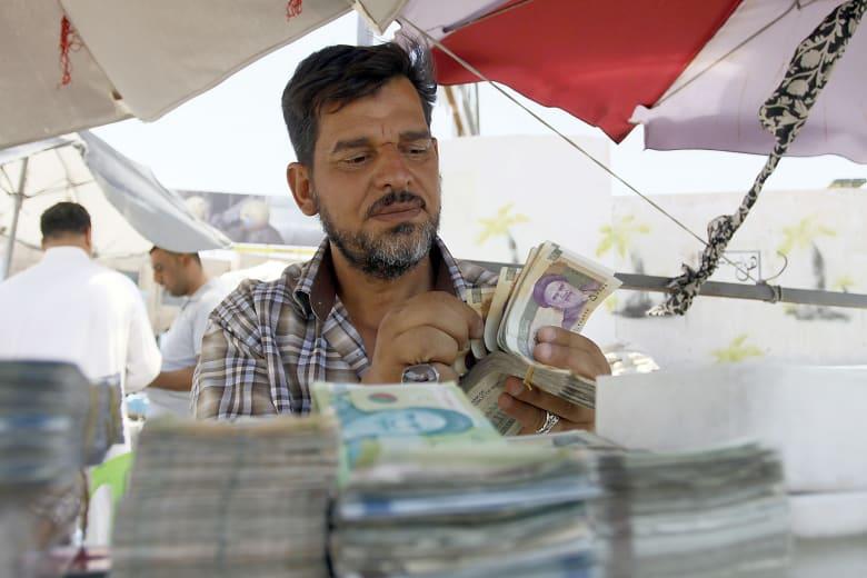 رجل يعد نقودا في إيران