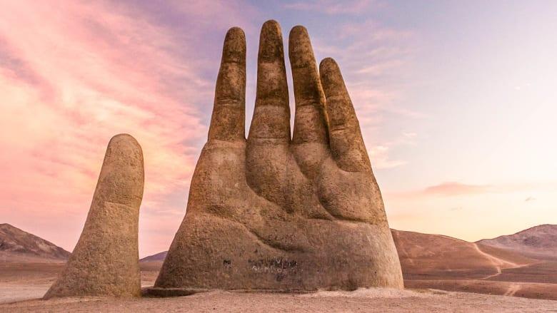 يد عملاقة تخرج من أرض الصحراء.. هل هي معلم أم سراب؟