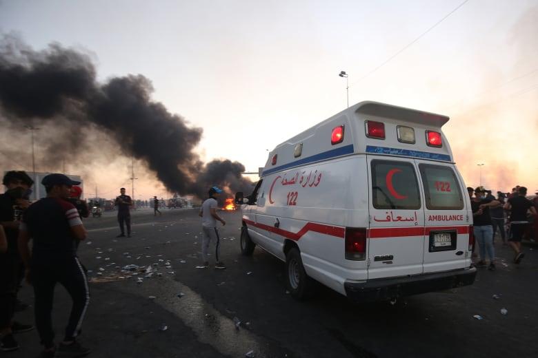 سيارة إسعاف وسط متظاهرين في بغداد لنقل ضحايا الاحتجاجات