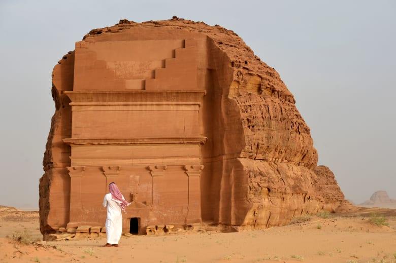 رجل يقف أمام القصر الفريد في مدائن صالح في السعودية