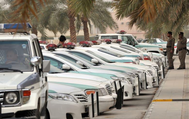صورة أرشيفية لسيارات الشرطة السعودية مع وجود عنصري أمن أمامهما