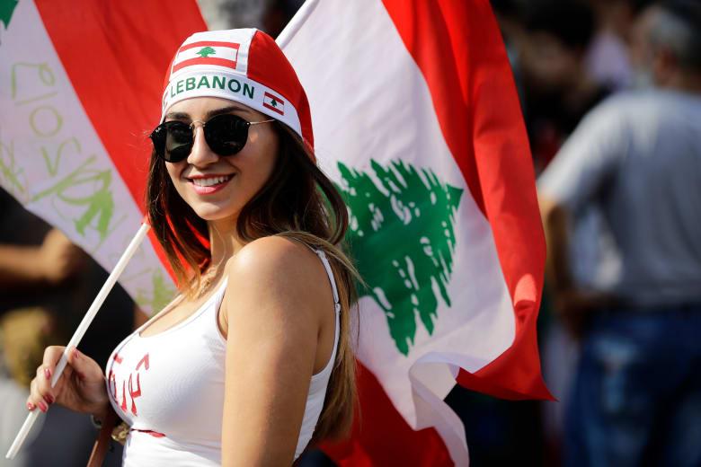 متظاهرة لبنانية تحمل العلم اللبناني على الطريق السريع الذي يربط بيروت بشمال لبنان، في زوق مصبح
