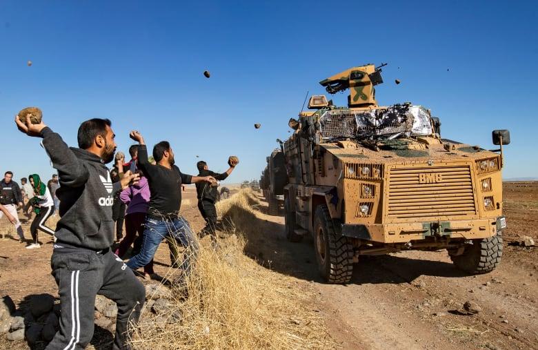 أكراد يقذفون مدرعة تركية بالحجارة في بلدة المعبدة شمال شرق الحسكة بسوريا