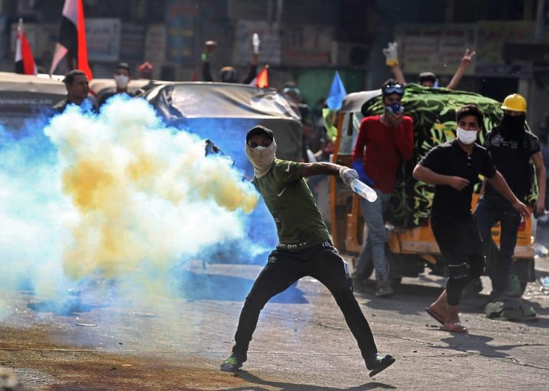 متظاهر عراقي يعيد إلقاء إحدى قنابل الغاز التي أطلقتها قوات الأمن العراقية باتجاه المحتجين في بغداد