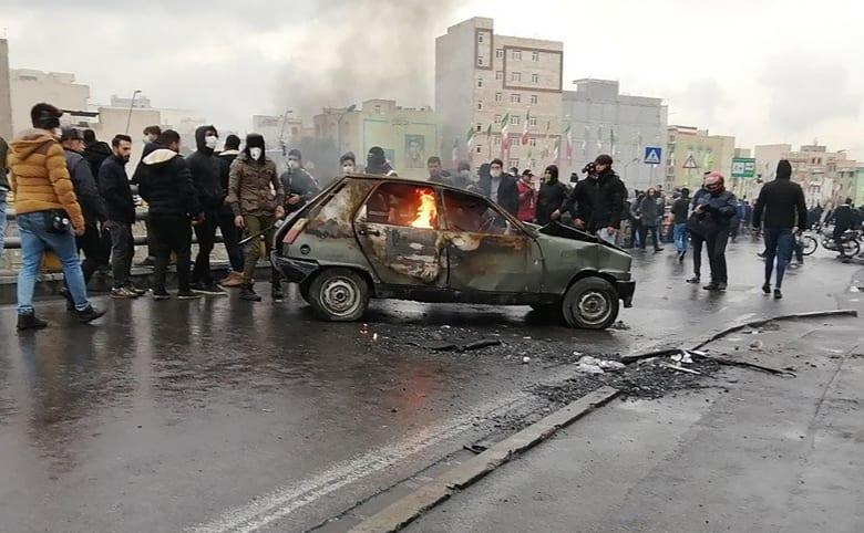 متظاهرون حول سيارة مشتعلة خلال الاحتجاجات في طهران